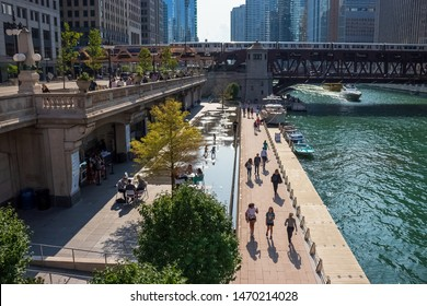 Chicago, IL / USA - 7/23/19:  People enjoy summer in Chicago on riverwalk, splash pad, boat, Wacker Dr., and el trail over Chicago River