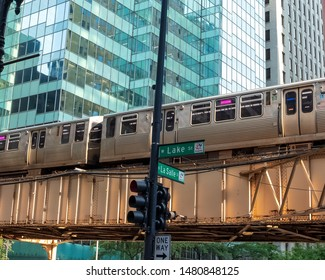 Chicago, IL / USA - 7/24/19: Pink line el train on elevated track traveling above the corner of Lake & LaSalle Streets in Chicago Loop.