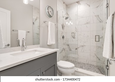 CHICAGO, IL, USA - APRIL 20, 2020: A beautiful, modern bathroom with a grey vanity and white granite counter top. Marble tiles line the white walk in shower with chrome hardware.