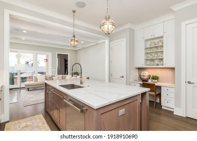 CHICAGO, IL, USA - APRIL 20, 2020: A beautiful, modern kitchen with white cabinets, wood island, and white granite counter tops. High end, stainless steel Wolf and Subzero appliances finish the space.
