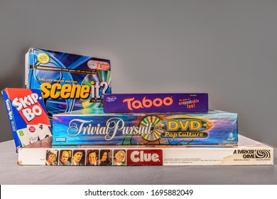 Chicago, IL / USA - April 5, 2020: Side view of a stack of vintage board and card games. Scene it, Skip Bo, Taboo, Trivial Pursuit, and Clue. Illustrative Editorial.