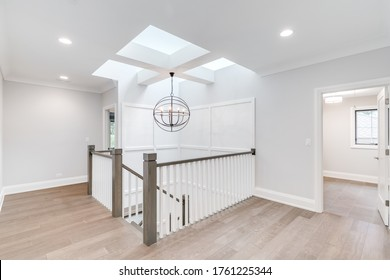CHICAGO, IL, USA - AUGUST 17, 2019:  An upstairs hallway with a staircase leading down. A fancy light hangs above the staircase with four sky lights pouring in light.