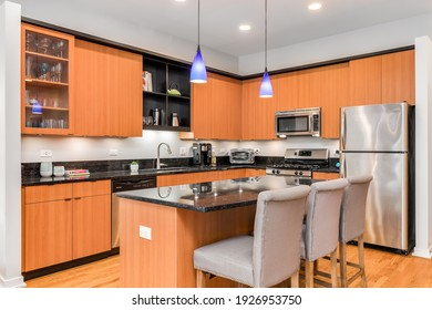 CHICAGO, IL, USA - AUGUST 31, 2020: A modern kitchen with wood cabinets, chairs sitting at a large island, stainless steel appliances, and black granite countertop.
