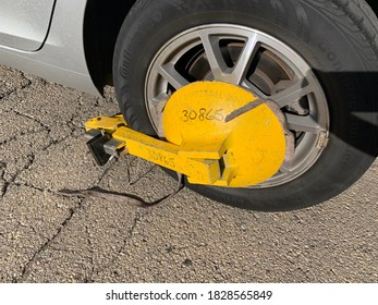 Chicago, Il USA - October 6, 2020. Car wheel blocked by wheel lock because illegal parking violation