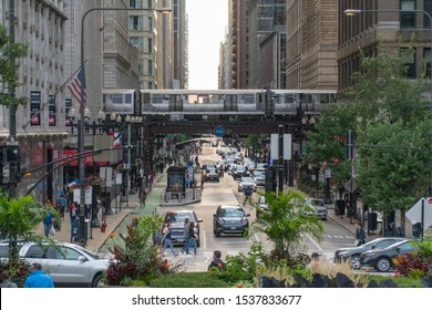 Chicago, IL, USA - Circa 2019: View down busy street in downtown as Loop train passes overhead tracks over avenue morning rush hour traffic and crowds of people walking down sidewalks to work