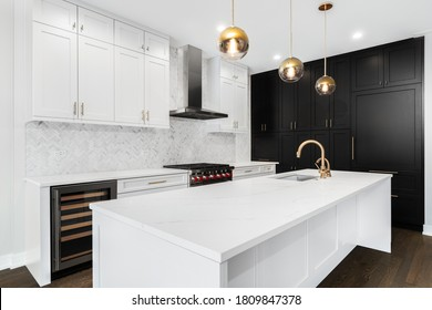 CHICAGO, IL, USA - DECEMBER 29, 2019: A luxurious, modern kitchen with white and black cabinets, gold hardware/faucets, and white herringbone marble tiles.