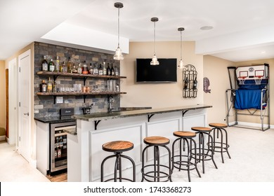 CHICAGO, IL, USA - FEBRUARY 24, 2020: A small basement bar /man cave with liquor on shelves and the bar is surrounded by wood bar stools. A basketball game is setup in the background.