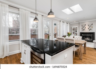 CHICAGO, IL, USA - FEBRUARY 6, 2020: Looking out from a condo kitchen with white cabinets and black granite towards a dining room and living room area.