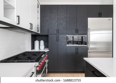 CHICAGO, IL, USA - FEBRUARY 8, 2020: A modern kitchen with black and white cabinets, stainless steel Wolf and Sub-Zero appliances, and bar stools sitting at the white granite counter top.