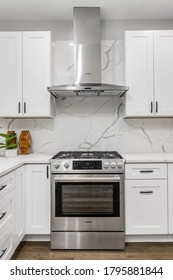 CHICAGO, IL, USA - JANUARY 22, 2020: Detail shot of a stainless steel Bosch stove and hood in an all white kitchen surrounded by a marble back splash.