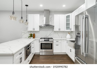 CHICAGO, IL, USA - JANUARY 22, 2020: A new, modern all white kitchen with black lights hanging from the ceiling and black bar stools sitting at the counter top for an eating area. Lights on.