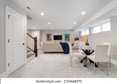 CHICAGO, IL, USA - JANUARY 27, 2020: A basement living and dining room area with modern furniture and stairs leading up. Pictures and a television are mounted on the wall.