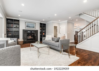 CHICAGO, IL, USA - JANUARY 27, 2020: A luxurious living room with a lit fireplace, built-in shelving, and cozy furniture with a view towards the staircase and kitchen.