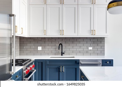 CHICAGO, IL, USA - JANUARY 6, 2020: Blue and white cabinets in a modern kitchen with a blue island and white granite counter top. Subway tiles make for a beautiful back splash.