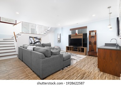 CHICAGO, IL, USA - JANUARY 6, 2021: A large, modern living room with a brown tiled floor, a large grey sectional couch, and stairs going up.