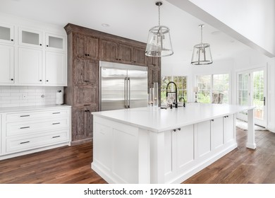 CHICAGO, IL, USA - JULY 21, 2020: A luxurious white kitchen stainless steel Wolf and Electrolux appliances, lights hanging above the large island, and granite countertops.