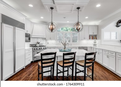 CHICAGO, IL, USA - JULY 22, 2019: A luxurious white kitchen that was remodeled to include Viking and Sub-Zero appliances and a granite kitchen island with bar stools. A window looks into living room.