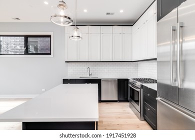 CHICAGO, IL, USA - JULY 4, 2019: A modern kitchen with white and black cabinets, stainless steel Bosch appliances, and light hardwood floors.