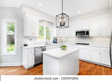 CHICAGO, IL, USA - JUNE 30, 2019: A bright kitchen with white cabinets, white granite counter tops, stainless steel appliances and light fixture hanging over the island. Limes to add a pop of color.