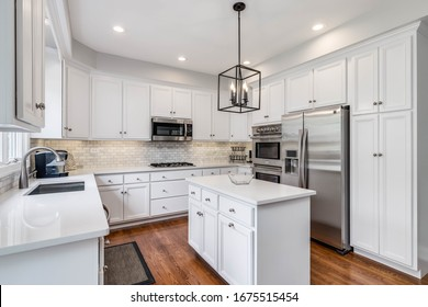 CHICAGO, IL, USA - JUNE 30, 2019: A bright kitchen with white cabinets, white granite counter tops, stainless steel appliances and light fixture hanging over the island.
