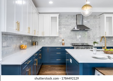 CHICAGO, IL, USA - JUNE 7, 2020: A luxurious white and blue kitchen with gold hardware, Bosch and Samsung stainless steel appliances, and white marbled granite counter tops.
