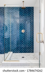 CHICAGO, IL, USA - JUNE 7, 2020: A blue single herringbone tiled shower in a luxury home with gold hardware.