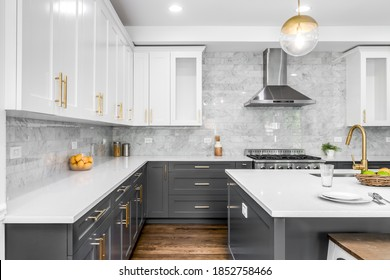 CHICAGO, IL, USA - JUNE 8, 2020: A luxurious white and grey kitchen with gold hardware, Bosch and Samsung stainless steel appliances, and white marbled granite counter tops.