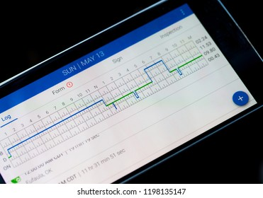 CHICAGO, IL, USA - MAY 14, 2018 - Electronic logging device for trucking industry with hours of service displayed on smarthphone screen