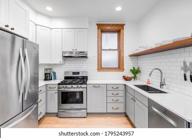 CHICAGO, IL, USA - MAY 20, 2020: A small kitchen in a downtown condo with white subway tile and white and grey cabinets.