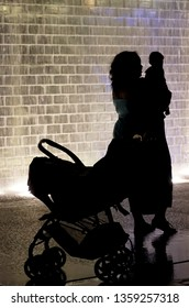 Chicago, IL, USA - May 24, 2018 - Silhouette of mother with baby and stroller against light wall from Crown Fountain in Millenium Park at night