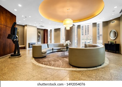 CHICAGO, IL, USA - May 28, 2019: A modern lobby waiting area in a downtown Chicago high rise with a wrap around couch and chandelier hanging down from the ceiling.