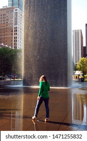 Chicago, IL, USA May 30, 2012 A young woman wades in the waters of the Crown Fountain in Millennium Park, Chicago