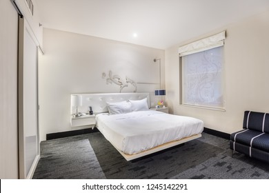 CHICAGO, IL, USA - NOVEMBER 3, 2018: An elegant bedroom in the W Chicago - City Center hotel featuring a white bed with an overhead light shining down and artwork on the wall.