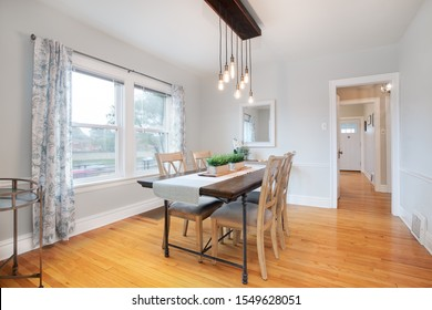 CHICAGO, IL, USA - OCT 2, 2019: A simple dining room with a fancy chandelier hanging from the ceiling over the table. The dark wood table is covered with a runner and two green plants sitting on top.