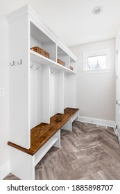 CHICAGO, IL, USA - OCTOBER 12, 2020: A modern farmhouse foyer or mud room with herringbone tiled floors, a white coat rack, and wooden bench.