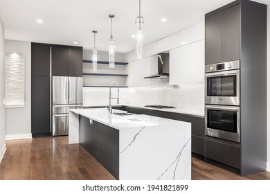 CHICAGO, IL, USA - OCTOBER 12, 2020: A modern, luxurious white and grey kitchen with Bosch stainless steel appliances, a waterfall granite island, glass pendant lights, and hardwood flooring.