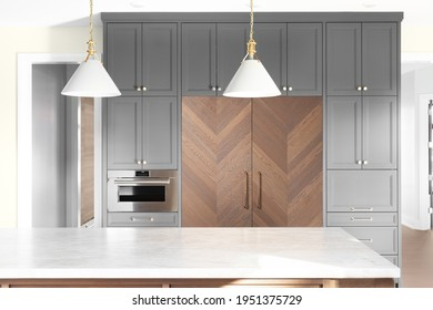 CHICAGO, IL, USA - OCTOBER 31, 2020: Grey kitchen cabinets and a herringbone wood covered Sub-Zero refrigerator in front of an island with white granite and pendant lights hanging above.