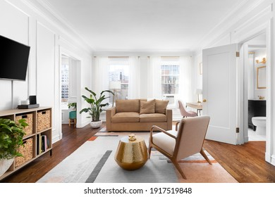 CHICAGO, IL, USA - SEPTEMBER 7, 2019: A bright, white living room in a downtown condo with cozy furniture, a television mounted on the wall, and a rug sitting on hardwood floors.