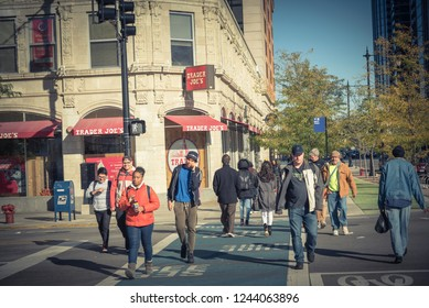CHICAGO, IL, US-OCT 17, 2018: Crowed of pedestrians walk past a Trader Joes's supermarket storefront in downtown intersection. An American neighborhood grocery store and discount retailer, own by ALDI