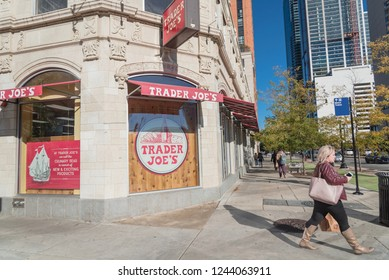 CHICAGO, IL, US-OCT 17, 2018: Customer with paper grocery bag exit Trader Joe's store near busy street in downtown Chicago. An American privately held chain of specialty grocery stores, own by ALDI