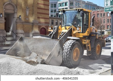CHICAGO, ILLINOIS - APRIL 15, 2016: Construction front loader operator grades gravel for West Illinois Street sewer replacement project.