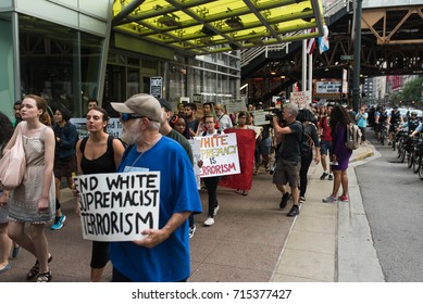 "CHICAGO, ILLINOIS - AUGUST 21, 2017: People protest against white supremacy and racism in downtown Chicago after the tragedy in Charlottesville. One sign stated ""White Supremacy is Terrorism""."