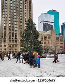 Chicago, Illinois, December 28, 2017. People walking and observing the Christmas tree, in front of the Chicago Tribune newspaper building, in the center of the city.