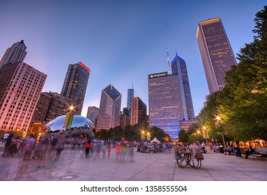 Chicago, Illinois - July 15, 2017: Millennium Park, Chicago. Tourists visit Cloud Gate in Millennium Park in the late afternoon, also known as the Bean is one of the parks major attractions.