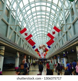 Chicago, Illinois - July 20, 2018: Flags on display as passengers walk to their gates at the K gates of Chicago O'hare International Airport's Terminal 3.