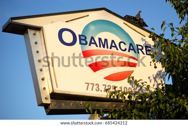 CHICAGO, ILLINOIS - JULY 22, 2017: [Pigeons rest on a sign advertising Obamacare]