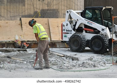 CHICAGO, ILLINOIS - JULY 25: Hispanic construction worker pneumatic jackhammers concrete next to Lake Street bridge on July 25, 2016 in near west Loop.
