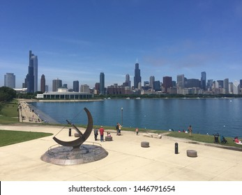 Chicago, Illinois; June 2019; The Chicago skyline on a beautiful sunny day, seen from outside the Adler Planetarium. On the foreground is a bronze bowstring equatorial sundial.