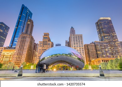 CHICAGO - ILLINOIS: MAY 12, 2018: Tourists visit Cloud Gate in Millennium Park in the late afternoon.