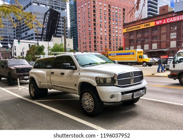 CHICAGO, ILLINOIS - OCTOBER 4, 2018: Work truck displays chrome spikes on wheel hubcaps nearby Kenzie street bascule bridge at river Fulton District.